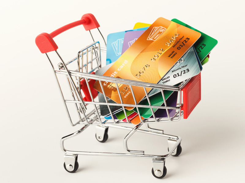 Shopping cart with credit cards isolated on white background